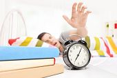 pic of early 20s  - Sleepy man reaching for the alarm clock seeping on a bed at home - JPG