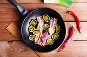 stock photo of bacon strips  - Strips of bacon in pan with shallot and chili pepper on wooden planks background - JPG