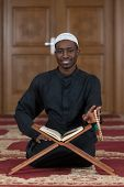 stock photo of muslim man  - Black African Muslim Man Reading Holy Islamic Book Koran  - JPG