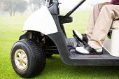 image of buggy  - Golfer driving his golf buggy at the golf course - JPG