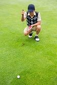 picture of ball cap  - Crouching golfer looking at the ball at the golfer course - JPG