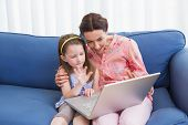 image of video chat  - Mother and daughter video chatting with laptop at home in the living room - JPG