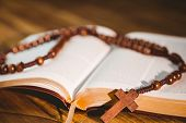 pic of evangelism  - Open bible with rosary beads on wooden table - JPG