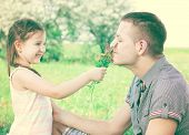 stock photo of uncle  - Little girl with flowers in hand and uncle smiling and enjoy in beautiful day - JPG