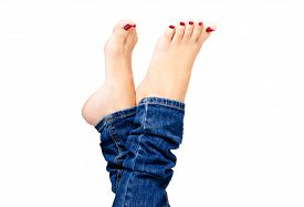 stock photo of human toe  - Beautiful female groomed feet with red nail polish in jeans closeup isolated on white background - JPG
