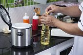 picture of chef cap  - Chef open cap of vegetable oil bottle before cooking - JPG