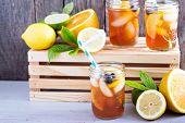 stock photo of mason  - Homemade iced tea in mason jars with straws - JPG