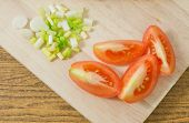 foto of scallion  - Vegetable Fresh Sliced Grape Tomatoes or Cherry Tomatoes with Chopped Scallions on Wooden Cutting Board - JPG