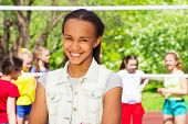picture of volleyball  - African teen girl and friends playing volleyball behind on the playground during sunny summer day - JPG