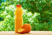 stock photo of orange  - Bottle of orange juice and the orange and the part of orange on the wooden table on the green blurred background - JPG