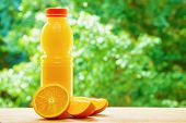 pic of orange  - Bottle with orange juice and the half of orange and the two orange lobules on the wooden table on the green blurred background - JPG