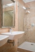 stock photo of shower-cubicle  - Shower cubicle and washbasin in beige washroom - JPG