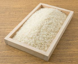 stock photo of rice  - Cuisine and Food Uncooked White Long Rice Basmati Rice or Thai Jasmine Rice in A Wooden Tray - JPG
