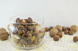 stock photo of decoupage  - Snack mix of nuts raisinshazelnuts almonds and chocolate in the bowl on a decoupage decorated table - JPG
