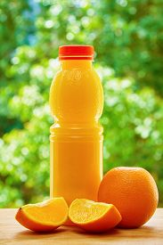 picture of orange  - Vertical photo of the bottle of orange juice and the orange and the two orange lobules on the wooden table on the green blurred background - JPG