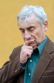 picture of frown  - Concerned caucasian senior man with his hand on his chin pondering frowning looking down - JPG