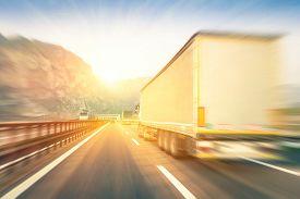 stock photo of trucks  - Generic semi trucks speeding on the highway at sunset  - JPG