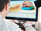 stock photo of computer-screen  - Analyzing  financial data and charts on computer screen - JPG