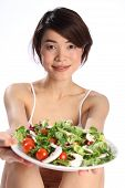 Girl holds out plate of green salad
