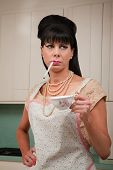 stock photo of early 60s  - Tough housewife in apron with cigarette and coffee cup - JPG