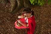 Little red riding hood picking mushrooms under a tree in the forest