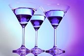 Three martini glasses on purple background