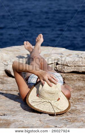 Постер, плакат: женщина с шляпу загорая на скалах у моря, холст на подрамнике