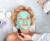 foto of mud pack  - Spa thermal mud face pack on woman face - JPG