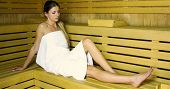 Young beautiful woman having a sauna bath in a steam room poster