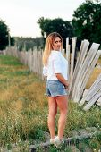Young Beautiful Blonde In A White Shirt And Short Denim Shorts Outdoors poster