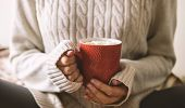 Womens Hands In Sweater Are Holding Cup Of Hot Coffee, Chocolate Or Tea. Concept Winter Comfort, Mo poster