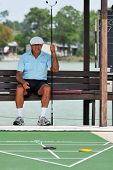 A senior man waiting for his turn at shuffleboard.