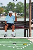 A senior man waiting for his turn at shuffleboard.