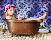 stock photo of clawfoot  - A beautiful preschooler blowing bubbles while wearing a bath bonnet in an old - JPG