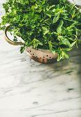 Bunch Of Fresh Green Garden Herbs In Brass Colander poster