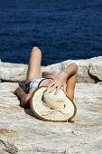 Постер, плакат: женщина с шляпу загорая на скалах у моря