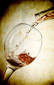 Red vine in glass on vintage background