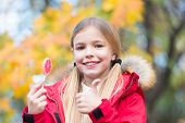 Trick Or Treat Sweet Candy. Kid Girl Wear Coat For Fall Season. Child Cheerful Eat Lollipop Candy Fa poster