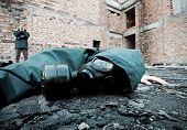 stock photo of gas mask  - Man with gas mask fallen on the ground - JPG