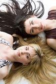 Two beautiful lying girls. Isolated on white background