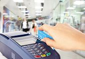 Human hand holding plastic card in payment machine in shop