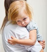 a mother is holding tight a sick girl.