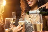 Hand pouring champagne from bottle into glasses with friends around him. Closeup of hand pouring whi poster