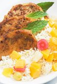 Caribbean style spicy pork chops with tropical fruit and cooked rice poster