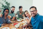 Group Of Happy Young Friends Enjoying Dinner At Home. Group Of Multiethnic Friends Enjoying Dinner P poster