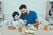 Happy Together. Man. Spends Time. Son. Father Of Boy. Engaged. Raising Child. Father Feeds His Son.  poster