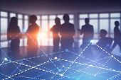 Silhouettes Of Diverse Business Team Members Working Together In Panoramic Office. Graph In The Fore poster