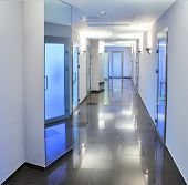 Long, empty corridor in a hospital or office building, with the ceiling lights reflected on the shin