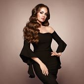 Beautiful Woman In Elegant Black Evening Dress. Brunette Girl With Long Healthy And Shiny Curly Hair poster