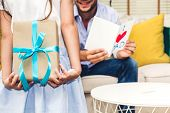 Little Daughter Giving Her Father A Blue Ribbon Gift Box For Surprise At Fathers Day.love Of Family poster